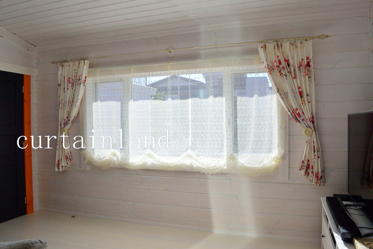 白いログハウスに赤い花の柄カーテン