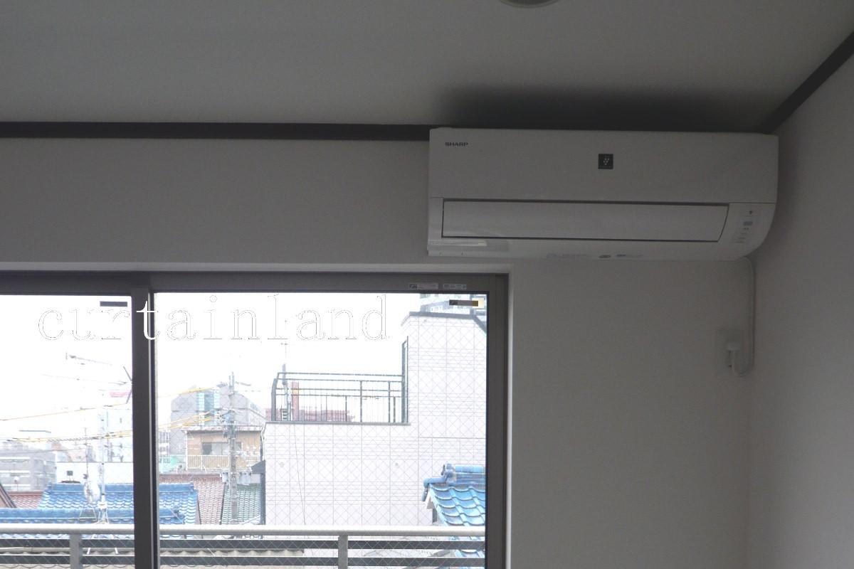 窓の上にエアコンが重なっている