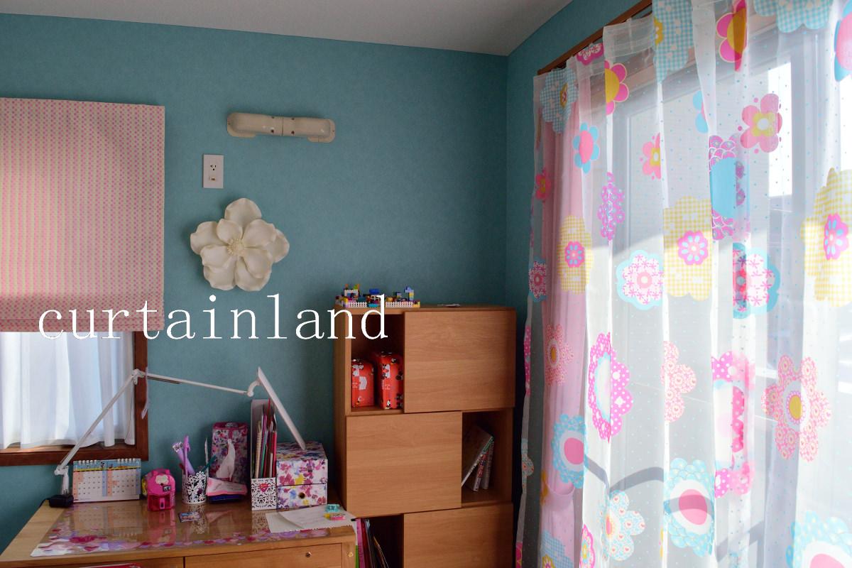 ブルーの壁紙にピンク系の花柄カーテン