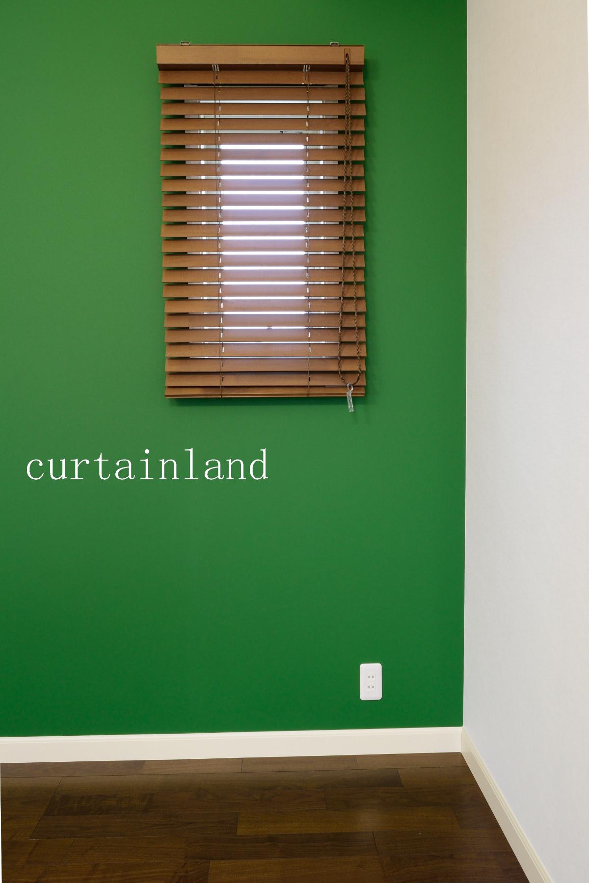 グリーンの壁に木製ブラインド