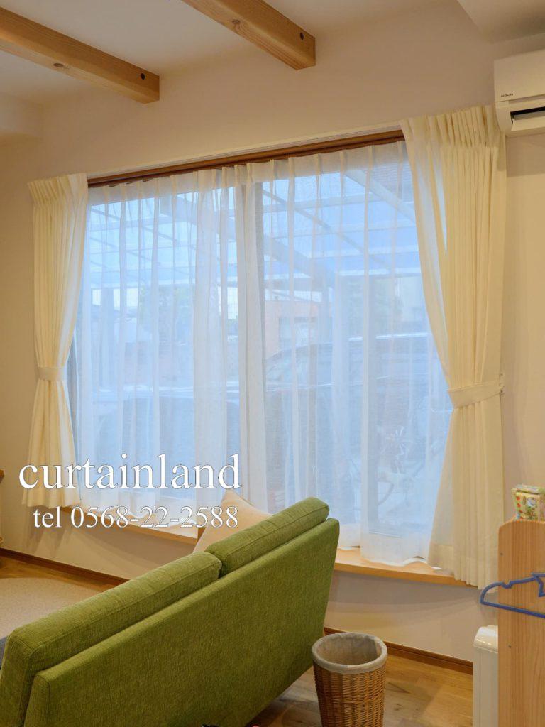 グリーンのソファとホワイトのリネンカーテン
