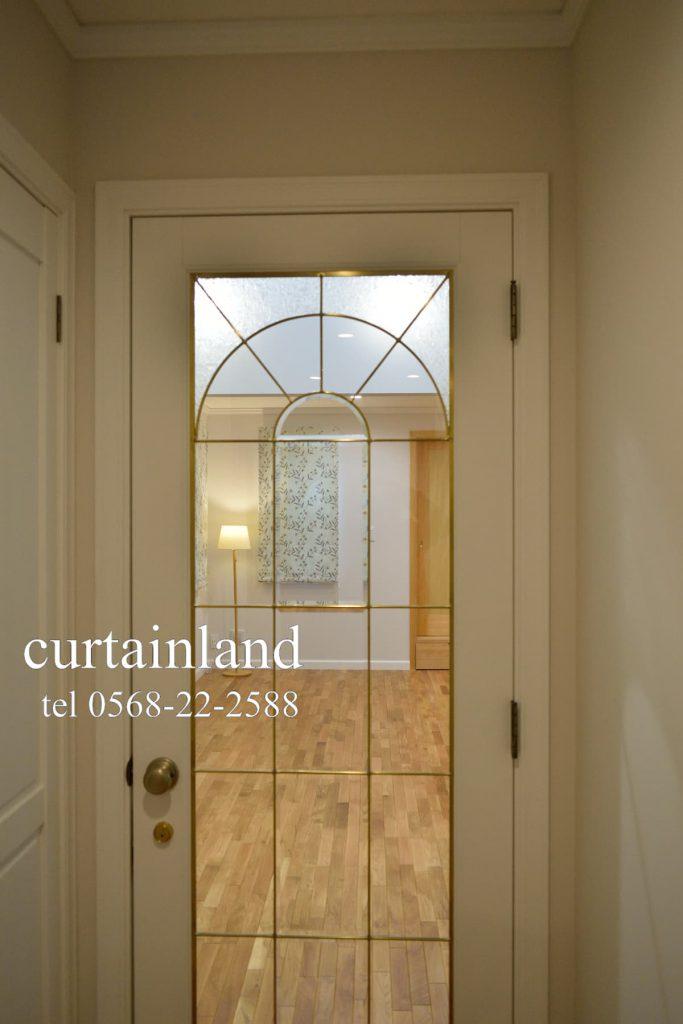 ステンドグラスの室内ドア越しに見える輸入住宅のLD